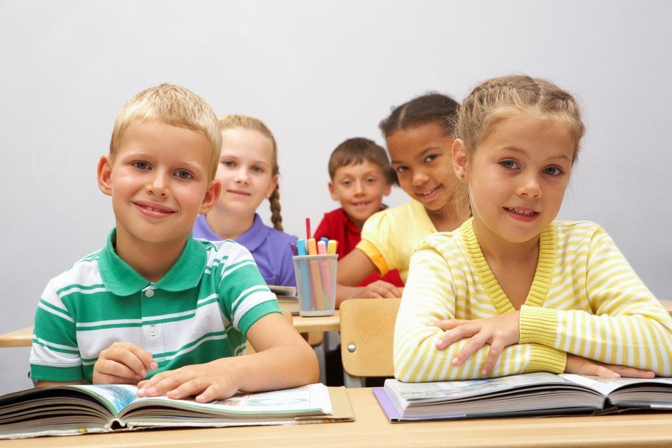 Portrait of smart pupils sitting in the classroom and looking at camera