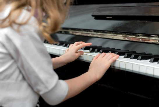 Child learns to play the piano.
