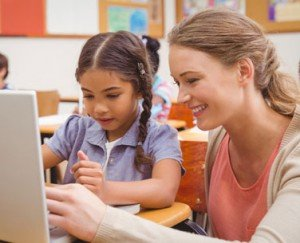 photodune-10183538-cute-pupil-using-computer-with-teacher-at-the-elementary-school-xs