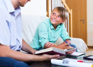 Happy teenager having private lesson with school teacher in living room at home
